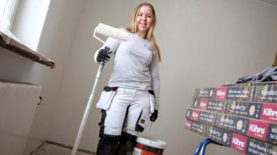 Jenny Störvold tittar mot kameran, omgiven av målarutrustning och med en lång roller i handen