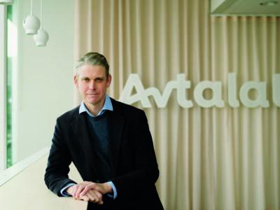 Niklas Hjert lutar sig mot en bänk med loggan för Avtalat på väggen i bakgrunden