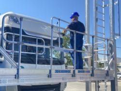 En person står på en ställning framför en lastbil