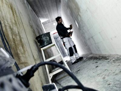 En person arbetar på en vägg i en kal korridor på ett bygge