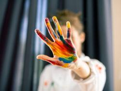 En kvinna håller upp en hand med målarfärg på i ett stopp-tecken