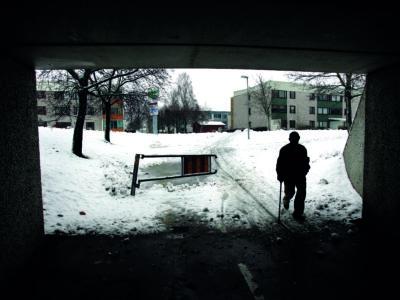 Svartvit silhuett av en person i motljus i en tunnelöppning
