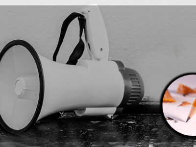 En vit megafon med en bild på papper och penna monterat över