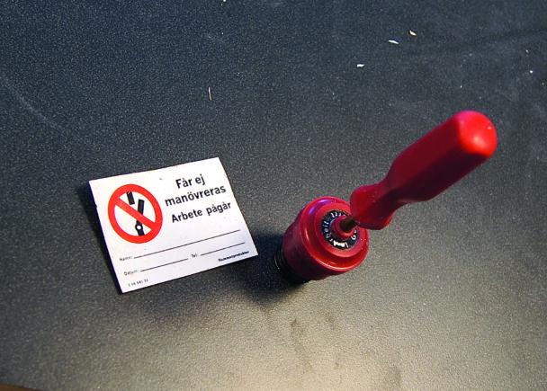En röd switch invid en varningsskylt