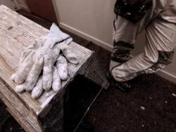 Ett par handskar på en låda, bredvid syns benen på en målare som lutar sig mot väggen.