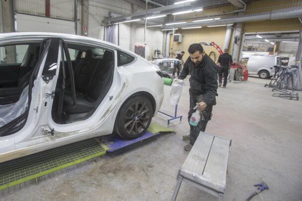 En person arbetar vid en bil med öppen dörr