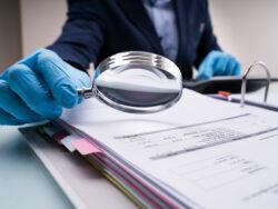 En person med skyddshandskar granskar ett dokument med förstoringsglas
