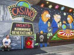 Max Gustafson sitter på marken framför en målad vägg med casino-tema