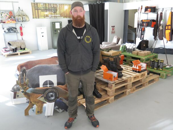 Sebastian Boussard framför lastpallar med jaktprodukter i butiken