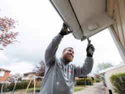 Ricky Johansson målar under ett tak utomhus.