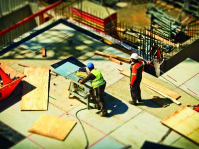 Två personer arbetar på ett bygge. Bilden ärt tilt-shiftad och de ser ut som miniatyrer.