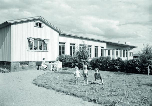 En svartvit bild på Petterslund från när det var nybyggt 1940. Några barn och vuxna står och sitter på gräsmattan.