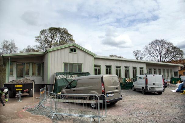 Petterslund sett utifrån: Ett långt vitt hus med gröna nockar och knutar