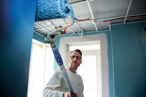 Peter Lager målar blått med en roller på skaft