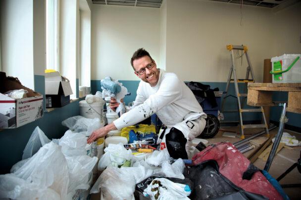 Peter Lager sitter på huk bland färgburkar och skyddsplast