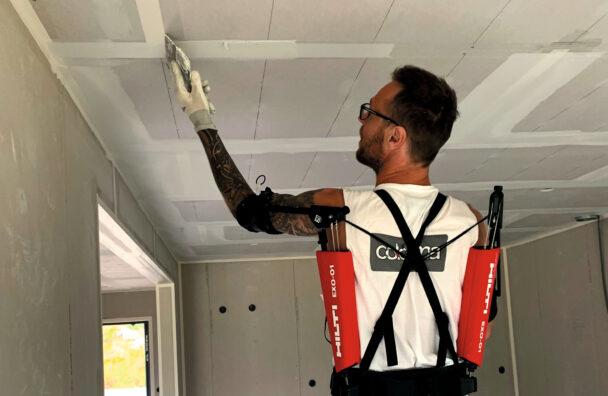 Johnny Brandborg målar ett tak med exoskelettet på sig