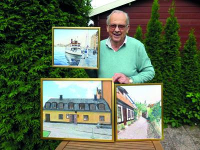 Lennart Almberg visar upp tre tavlor utomhus