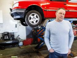 Roberth Forsberg framför en röd bil i verkstaden