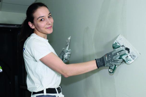 Mihaela Ciobanu jobbar med en skrapa på en vägg