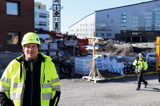 Jan-Crister Riggo i gul hjälm och jacka utomhus vid bygget