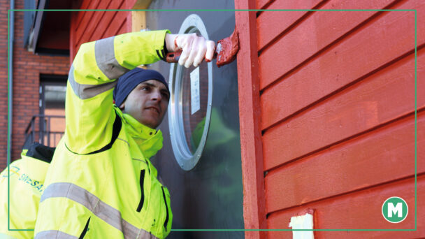 A painter in a yellow jacket is panting a red door frame.