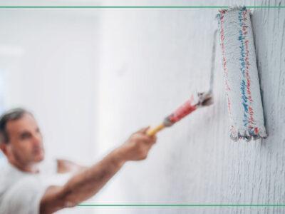 En person måloare en vägg med en roller