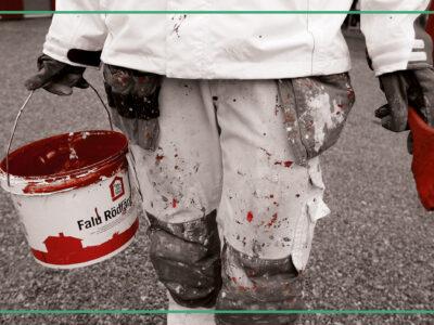 En person går med en hink falu rödfärg och en pensel