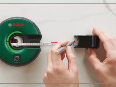 Två händer mäter en vägg med lasern