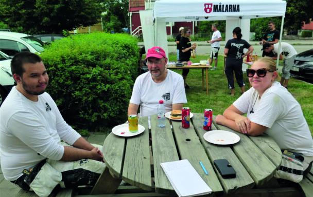 Joakim Sund, Micke Hellman och Nora Holmgren Sjöberg sitter vid ett bort utomhus