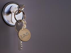 """En nyckelknippa i ett dörrlås. På nyckelbrickan står det """"LAS"""""""