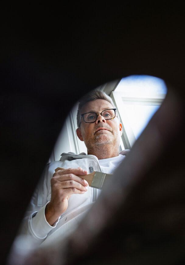 Henrik Karlsson sedd genom springan i en fönsterbräda