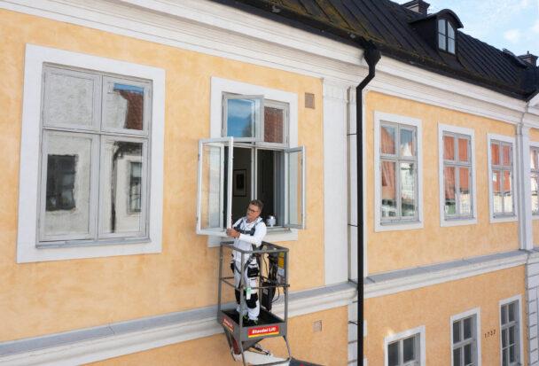 Henrik Karlsson i en skylift vid en husfasad