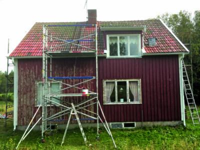 En röd trävilla med byggnadsställning vid fasaden.